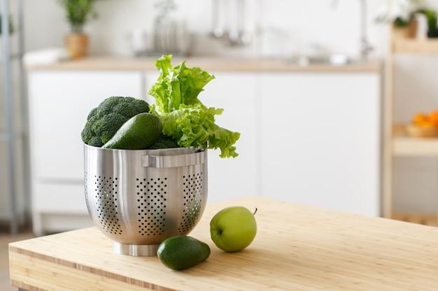 Vegetais verdes na mesa da cozinha. comida saudável. tiro do estúdio.