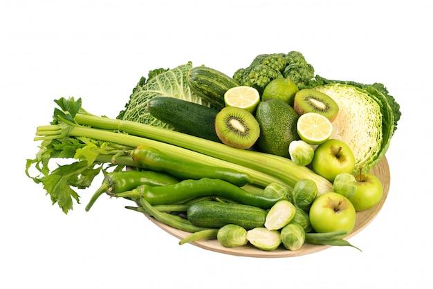 Vegetais verdes na placa de madeira no fundo branco