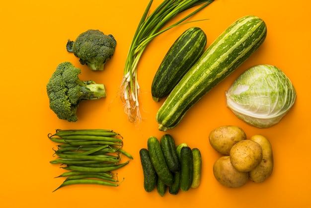 Vegetais verdes no conceito colorido de fundo amarelo, vista superior, batatas, brócolis, pepino, cebola, repolho, abobrinha, feijão