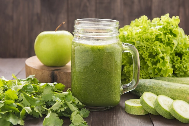 Vegetais verdes saudáveis e smoothie da fruta verde na mesa de madeira rústica
