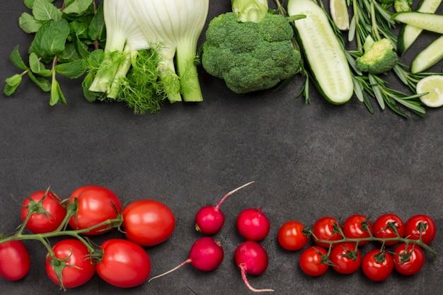 Vegetais verdes, tomates vermelhos e rabanetes. fundo preto. postura plana.