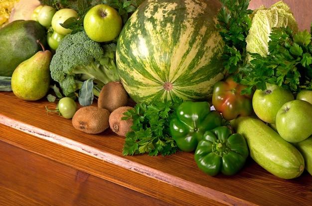 Vegetais verdes úteis em um fundo de madeira.