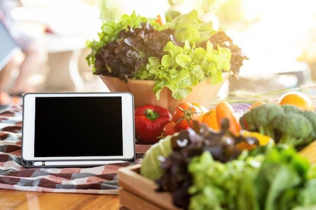Vegetal cru e fruta orgânicos frescos na bacia para a salada e a tabuleta na tabela.