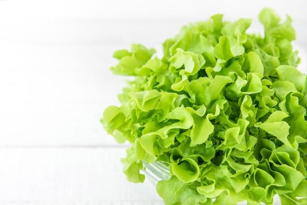 Vegetal de alface verde orgânico no balcão da cozinha de madeira branca