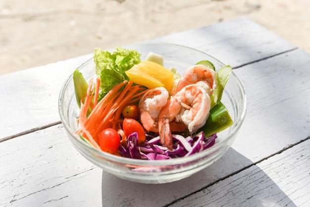 Vegetal de salada - camarão de salada com frutas e alface fresca tomate cenoura pimentão na tigela na mesa comida saudável comer conceito