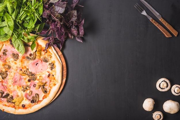Vegetal folhoso; cogumelo e pizza com talheres em pano de fundo escuro