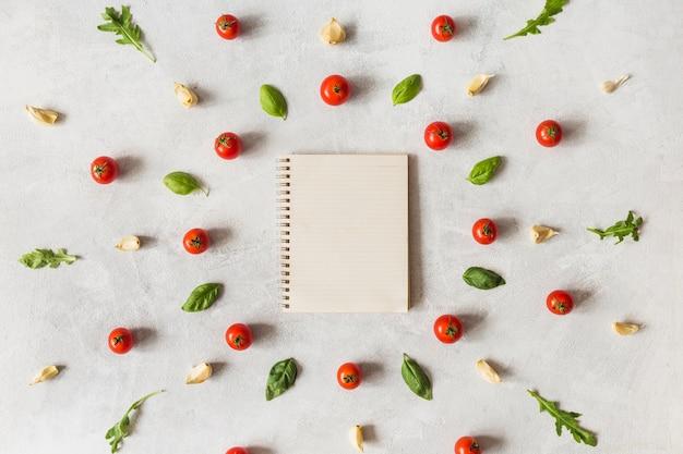 Vegetal orgânico fresco, organizado em torno do caderno espiral no pano de fundo texturizado