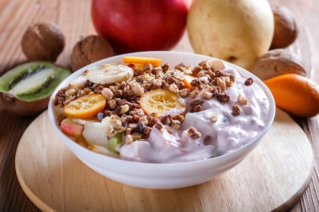 Vegetariana salada de bananas, maçãs, peras, laranjas, kiwi com granola e iogurte em madeira marrom
