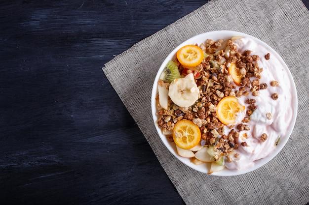 Vegetariana salada de bananas, maçãs, peras, laranjas, kiwi com granola e iogurte em madeira preta