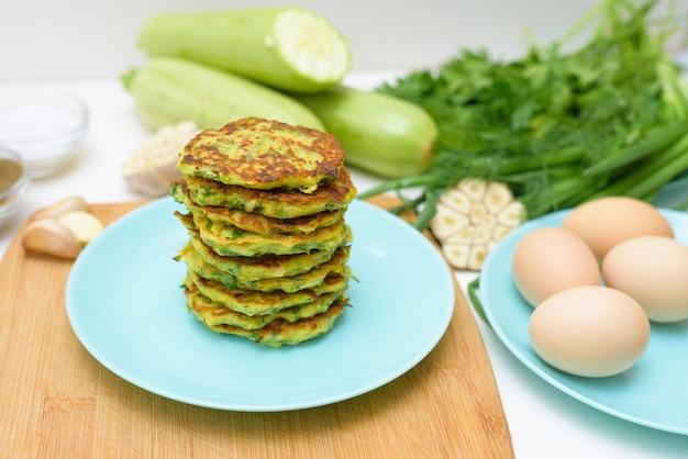 Vegetariano frito panquecas com abobrinha e verdes num prato azul