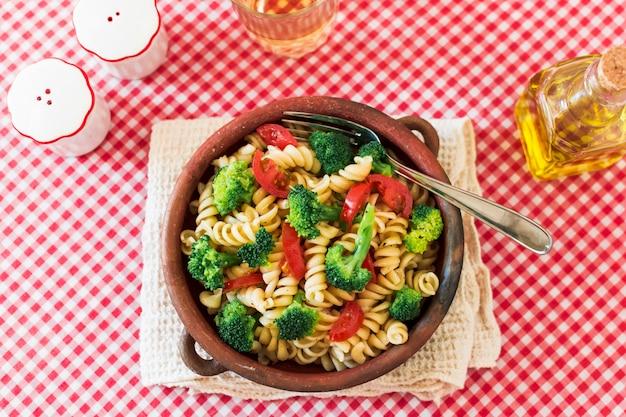 Vegetariano macarrão fusilli com tomate e brócolis na toalha de mesa