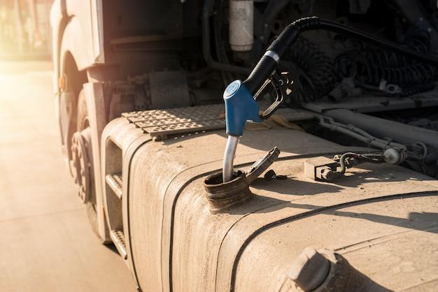 Veículo caminhão sendo reabastecido no posto de gasolina.
