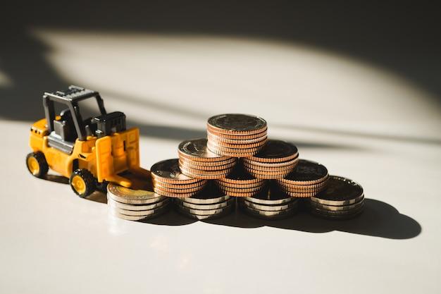 Veículo de empilhadeira em miniatura, trabalhando com pilha de moedas