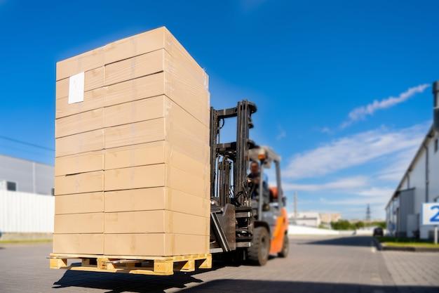 Veículo de empilhadeira manipulando mercadorias na área de logística fora do armazém.