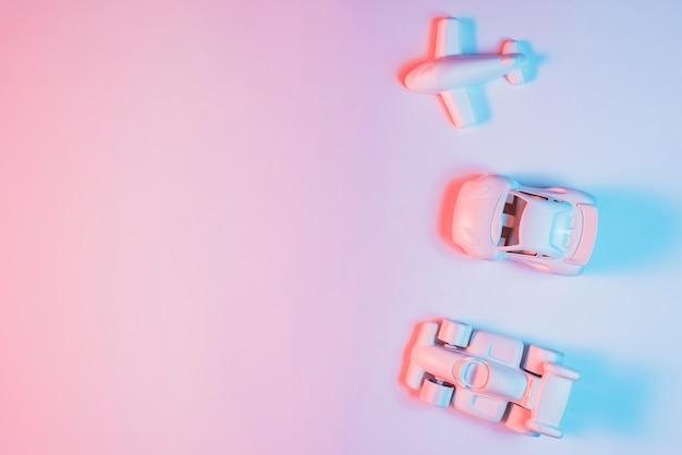 Veículo de transporte em miniatura organizado em uma linha no pano de fundo rosa