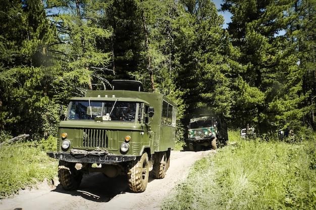 Veículo militar na floresta, antigos veículos militares russos dirigindo em uma estrada de terra em mau estado através da taiga