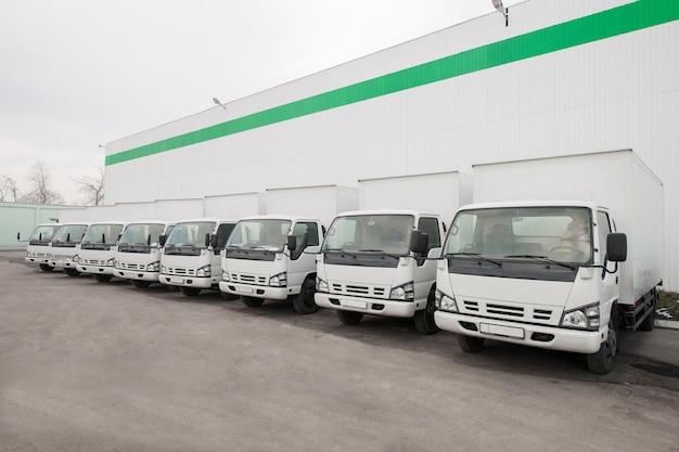 Veículos de carga ficam em uma fila em um estacionamento perto do armazém da fábrica caminhão no armazém
