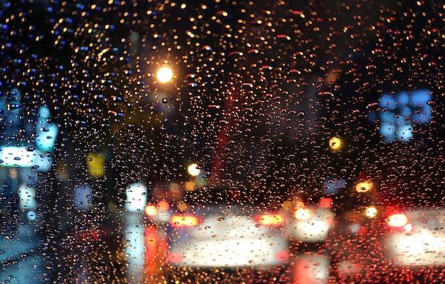 Veículos turva e lanternas traseiras vistas através das gotas de chuva no pára-brisas do carro à noite