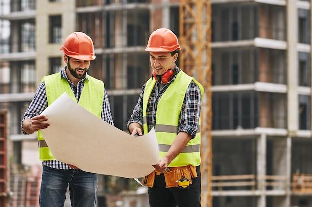 Veja aqui dois jovens construtores em uniforme de trabalho e capacetes segurando um desenho de construção