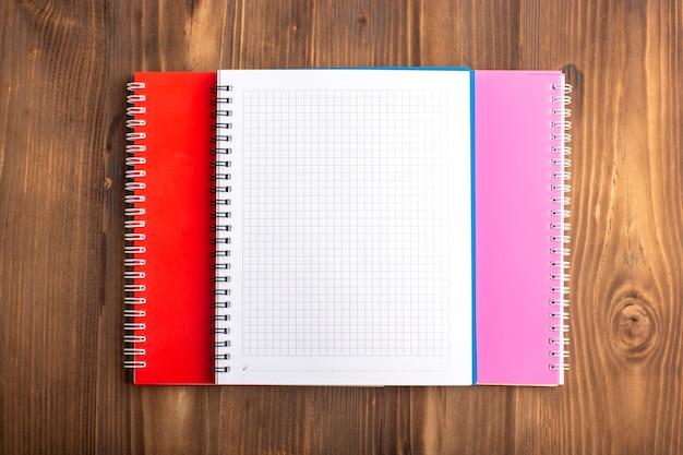 Veja de cima diferentes cadernos na mesa marrom