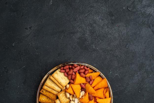 Veja de cima diferentes salgadinhos, biscoitos, nozes e batatas fritas na superfície cinza-escura