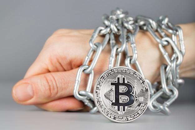 Veja em bitcoin. mão amarrada por uma corrente metálica no fundo. fechar-se