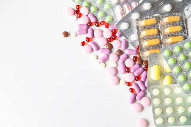 Veja em comprimidos espalhados e comprimidos em embalagens em fundo branco.