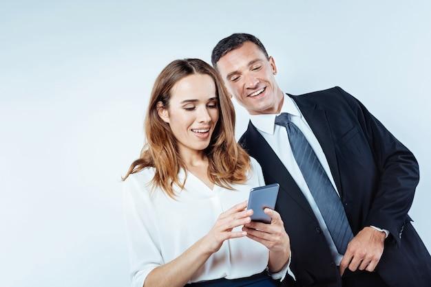 Veja isso. colega de trabalho do sexo masculino alegre em pé ao lado de sua colega e sorrindo enquanto concentra sua atenção em uma tela de seu telefone e olhando as fotos.
