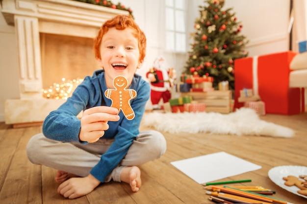 Veja isso. garoto pré-adolescente radiante olhando para a câmera com entusiasmo enquanto está sentado no chão e mostrando um saboroso biscoito de gengibre para a câmera.