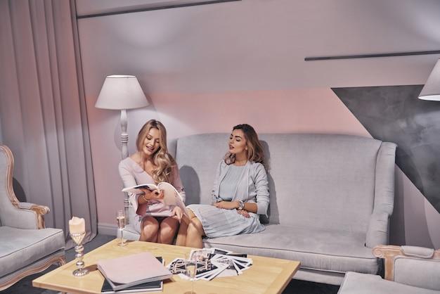 Veja isso! mulheres jovens atraentes em vestidos elegantes escolhendo um vestido do catálogo enquanto estão sentadas no sofá na loja de noivas