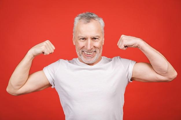 Veja isso! músculo apresentando homem sênior. homem envelhecido, flexionando os braços isolados. alegre animado moderno legal pensionista vovô praticando musculação.