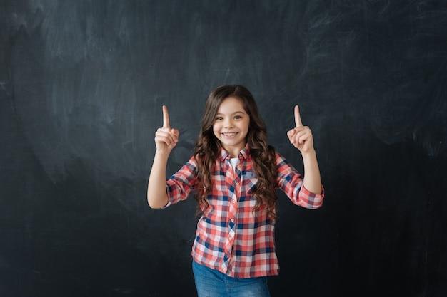 Veja isso. sorrindo feliz e linda garota parada no quadro-negro apreciando o desenho imaginário enquanto aponta os dedos para cima