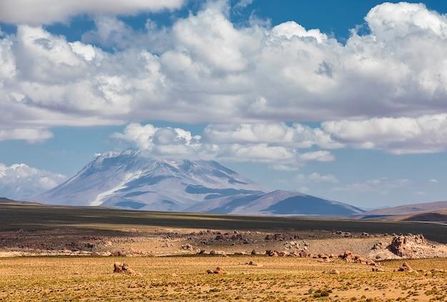 Veja o deserto e o vulcão com nuvens dramáticas em potosi, bolívia