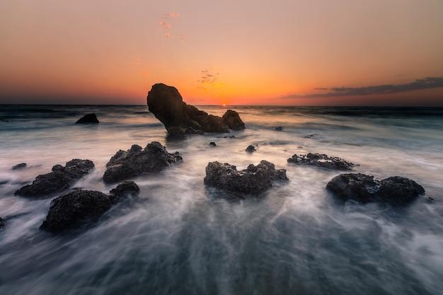 Veja o pôr do sol na praia de pedras de ilbarritz em biarritz, no país basco.