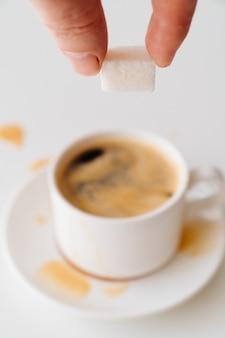 Veja o topo. xícara de café com leite e açúcar cúbico na mão. café da manhã tradicional. vivacidade nas subidas matinais. cappuccino
