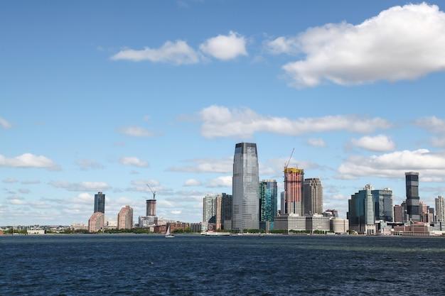Veja o veleiro de cruzeiro nos edifícios do porto de nova york da ilha de manhattan ao fundo