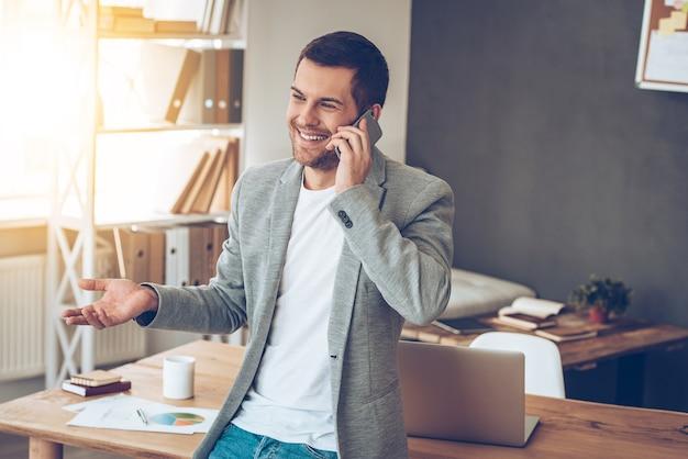 Vejo você no meu escritório! jovem bonito falando no celular com um sorriso enquanto se inclina para a mesa em seu escritório