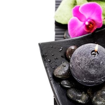 Vela acesa com gotas de água e pedras