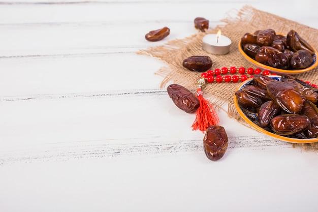 Vela acesa com placa de datas suculentas e contas de oração vermelhas na mesa de madeira