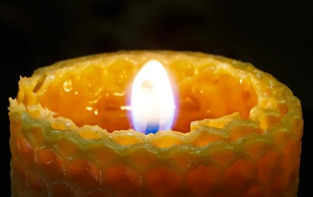 Vela acesa do favo de mel em fundo escuro.