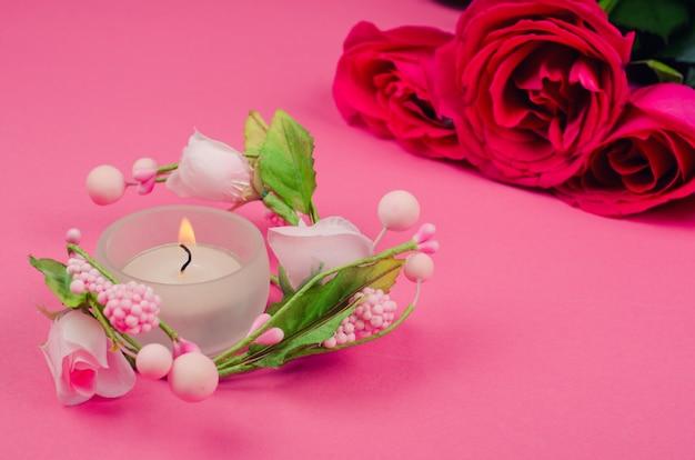 Vela acesa e rosas cor de rosa e vermelhas