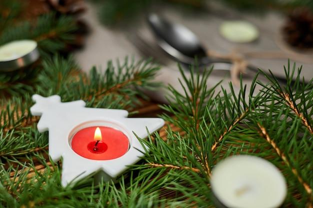 Vela acesa em uma árvore de natal em uma mesa de natal servida contra ramos de pinheiro e cones