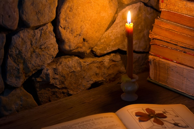 Vela acesa na mesa e livros antigos