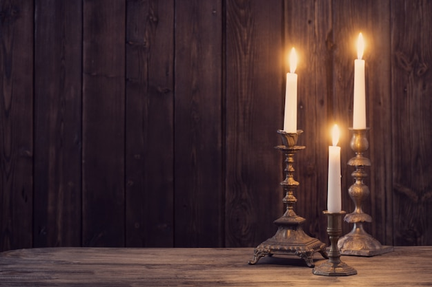 Vela acesa na velha madeira escura