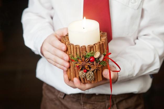 Vela acesa nas mãos de um menino. decoração de natal. mãos de criança segurando uma vela linda com fogo. época de natal. feriados de ano novo e inverno