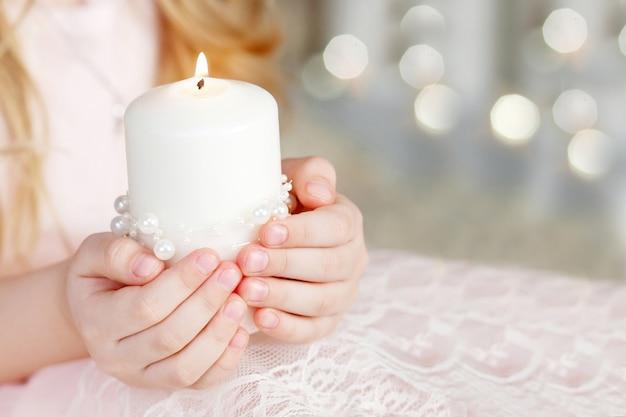 Vela acesa nas mãos de uma menina. vela de natal. decoração de natal. mãos de criança segurando uma vela linda com fogo. copie o espaço