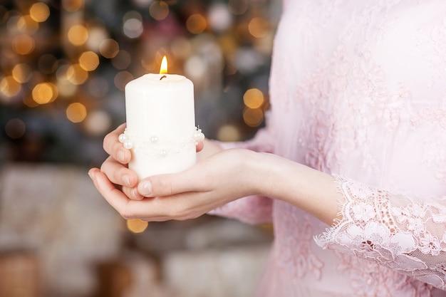 Vela acesa nas mãos de uma menina. vela de natal. decoração de natal. mãos de crianças segurando uma vela linda com fogo