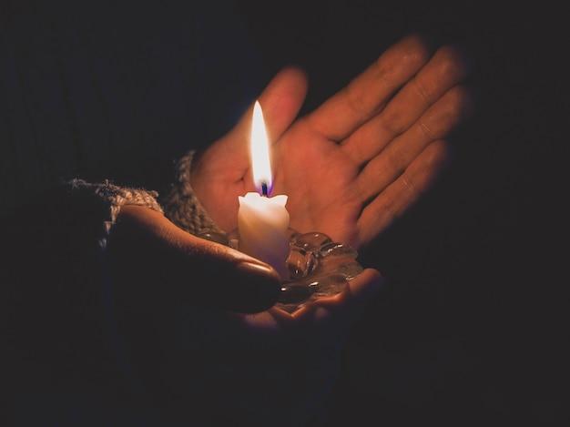 Vela acesa nas mãos femininas à noite.