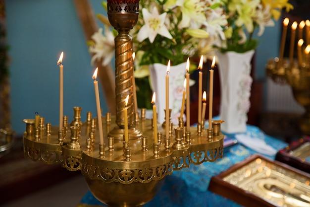 Vela amarela acendeu o fogo para o culto. queimando velas de cera na igreja