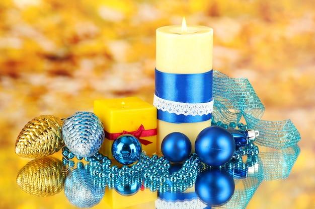 Vela amarela com decoração de natal em fundo brilhante